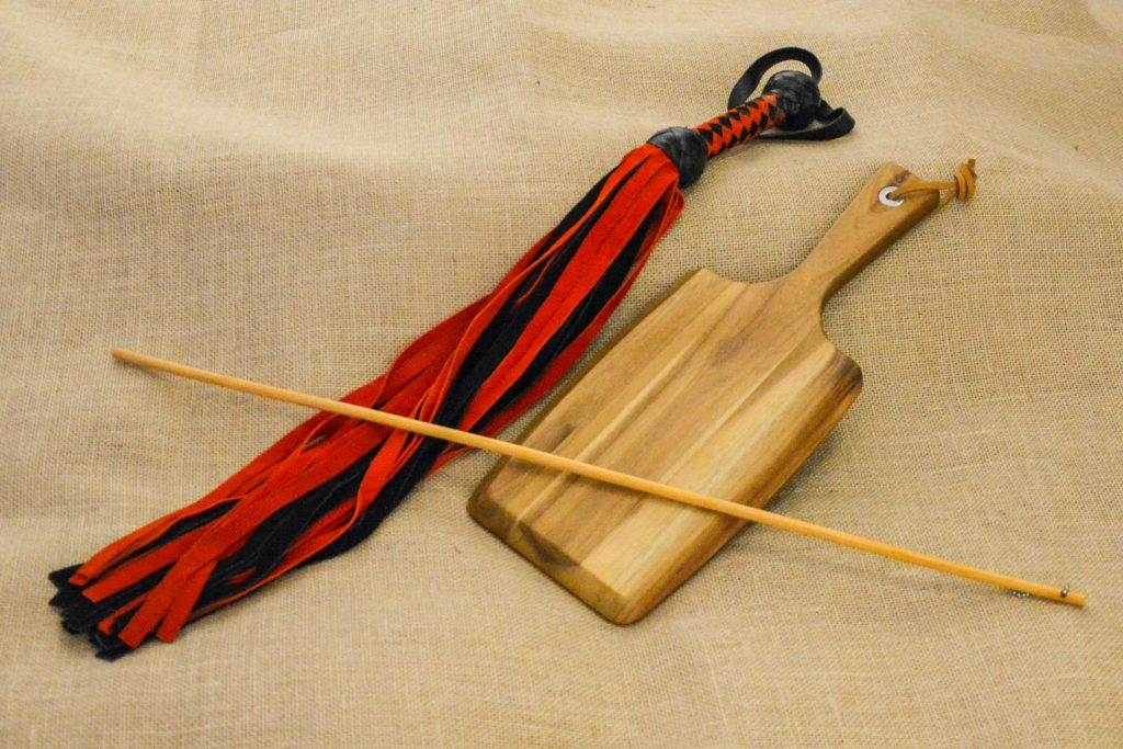 Photo by Liz BlackX  On the photo you see a black and red flogger, a bamboo cane and a paddle.