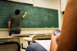Teacher writing on a blackboard  while you see a student texting in the forefront.